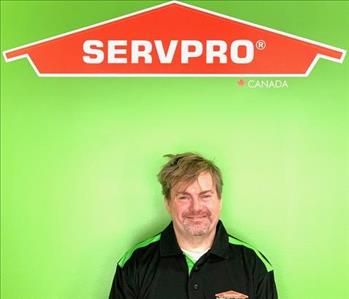 Project Manager Standing Next to Our SERVPRO logo